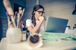 Frau sitzt am Laptop und hat Stress